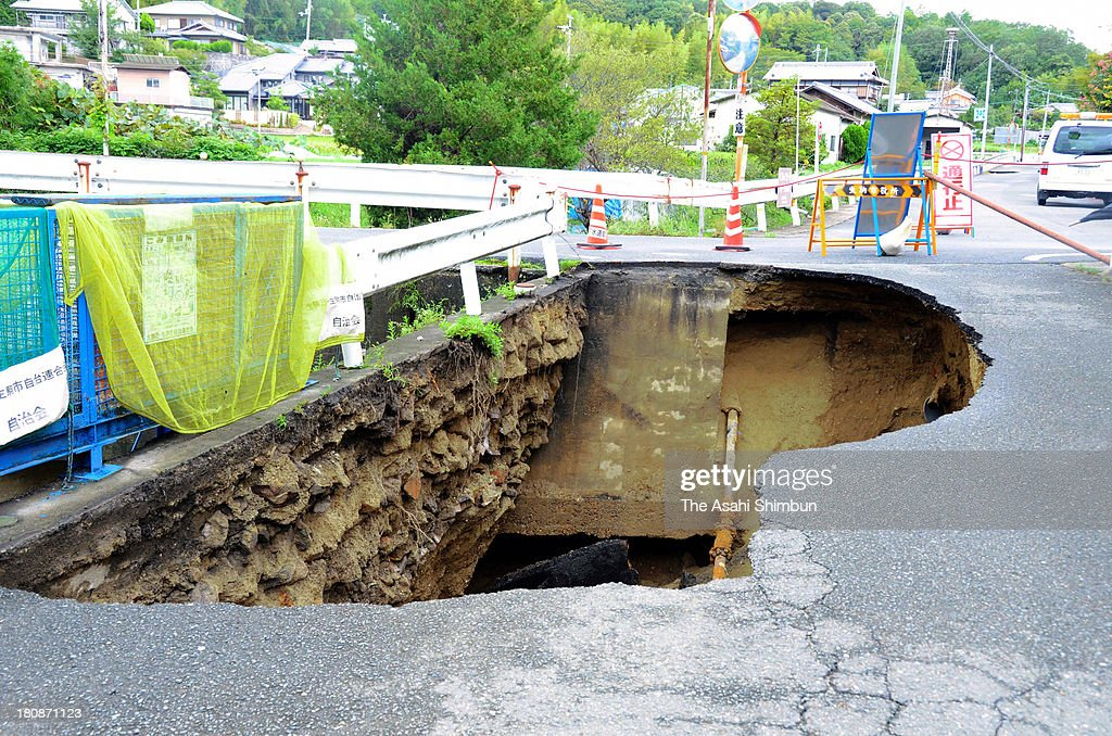 A road is damaged by heavt rain triggered by typhoon Man-Yi approaching on September 16, 2013 in Ikoma, Nara, Japan. The storm hit land near Toyohashi, Aichi Prefecture, before 8 a.m. and moved along Honshu throughout the day, damaging buildings, disrupting transportation and causing blackouts, three killed and five missing.