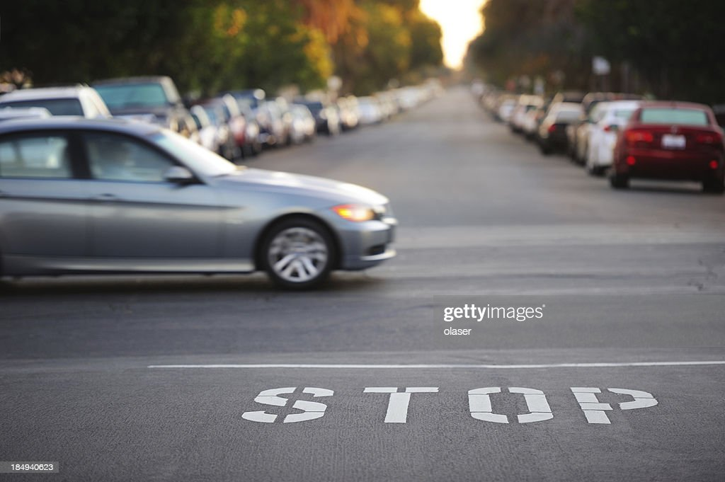 'Road junction, stop word, motion blurred car'