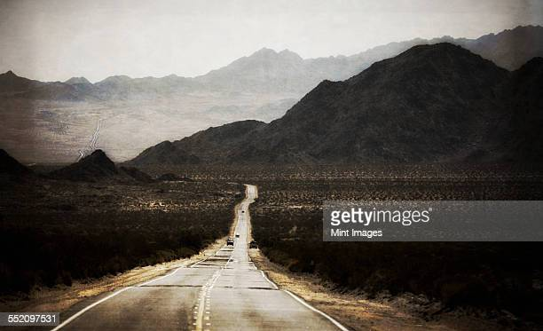 A road leading into the distance, to a range of mountains. Desert scenery, cars on the road.