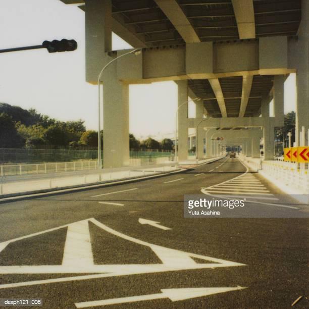 Road markings on road below highway