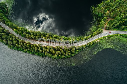 Camino en una estrecha franja de tierra entre dos lagos con bosque : Foto de stock