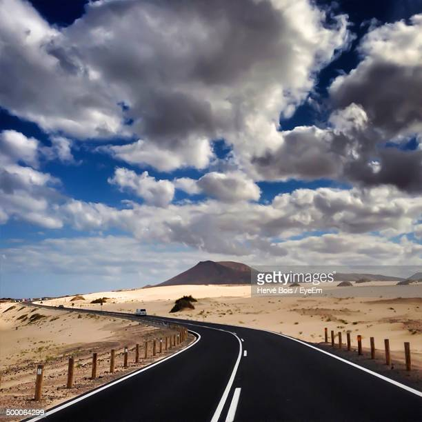 Road passing through the desert against cloudy sky