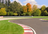 Pronounced curve on a road racing closed circuit on a beautiful autumn day.