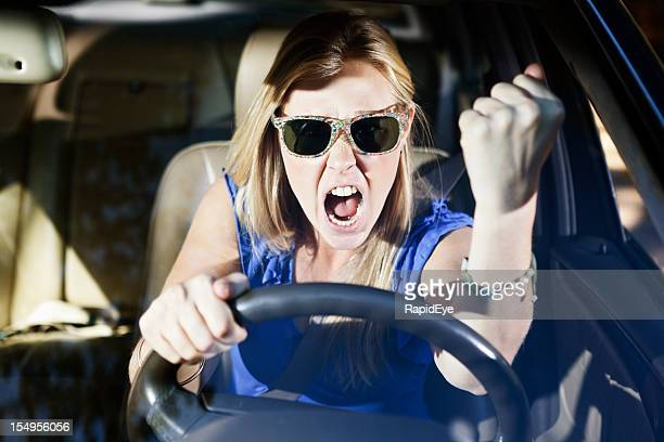 Road rage! Beautiful blonde driver shakes her fist in fury