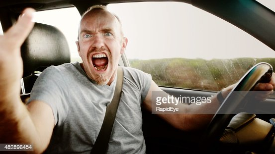 Road rage: furious male driver shouting, waving, and yelling