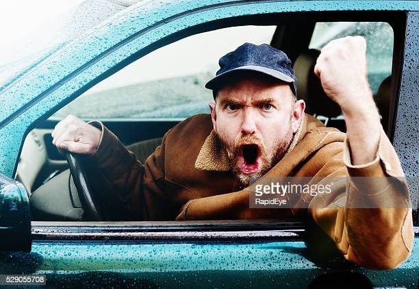 Rage au volant  : Furieux homme conducteur crier, menacer du poing à travers une fenêtre