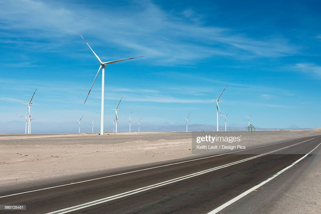 A road running beside a field full of wind turbines