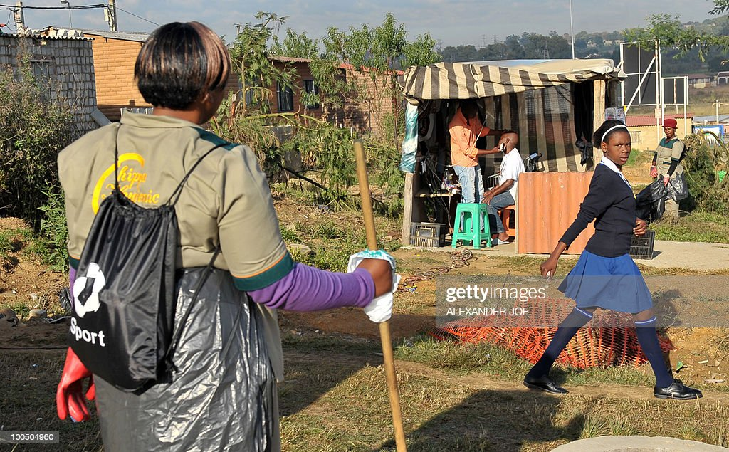 A road side hair dresser shaves a customer in the township of Alexandra in Johannesburg on May 7, 2010. All of the street names in the township have a football flavour like Striker street or Football street.