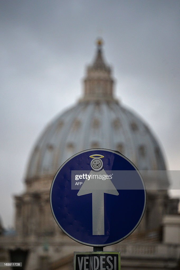 A road sign and a placard reading 'To sell' are dispayed outside St Peter's square with the dome of St Peter's basilica in the background March 11, 2013 in Rome. Catholic cardinals had a final day of talks on Monday before going into lockdown in the Sistine Chapel to elect a new pope after Benedict XVI's shock resignation, with an Italian and a Brazilian among the top contenders.