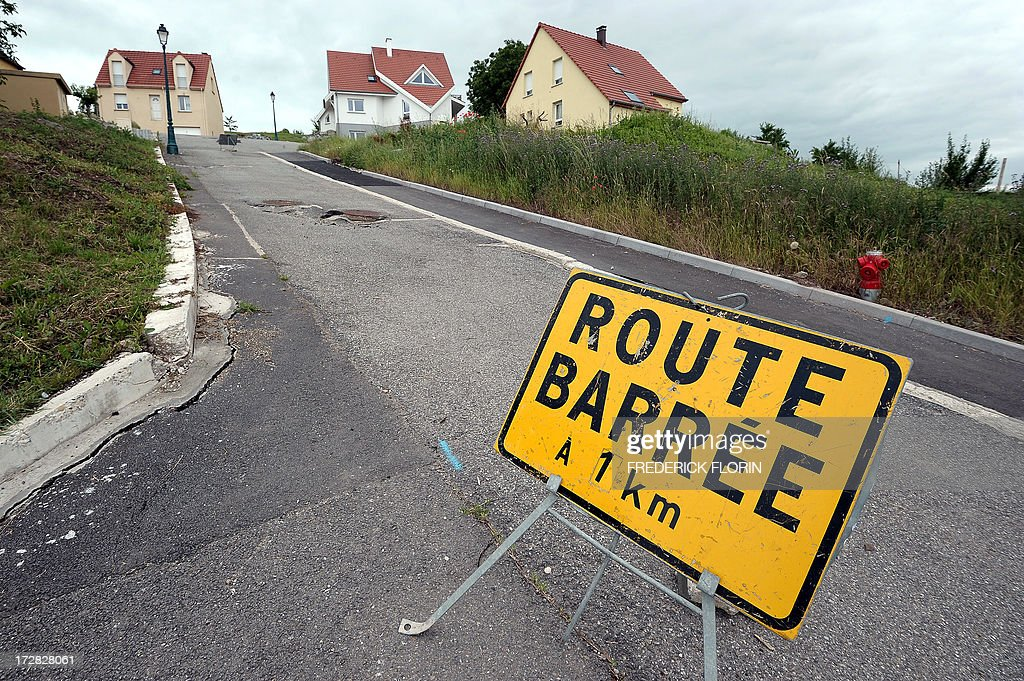 A road sign blocked a street of the village of Lochwiller, eastern France, on July 04, 2013. Leaning houses, cracks on walls, damaged streets : the ground moves in Lochwiller, where worried inhabitants are afraid that their village becomes uninhabitable. At the origin of the phenomenon, a 100-meter (328-feet) geothermal drilling in a private garden, according to experts. AFP PHOTO/FREDERICK FLORIN
