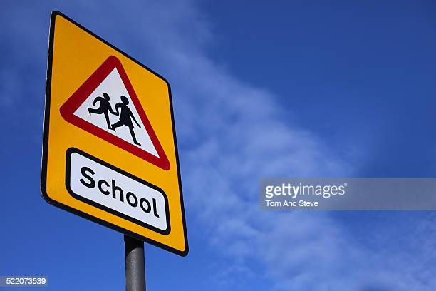 Road sign displaying school and children