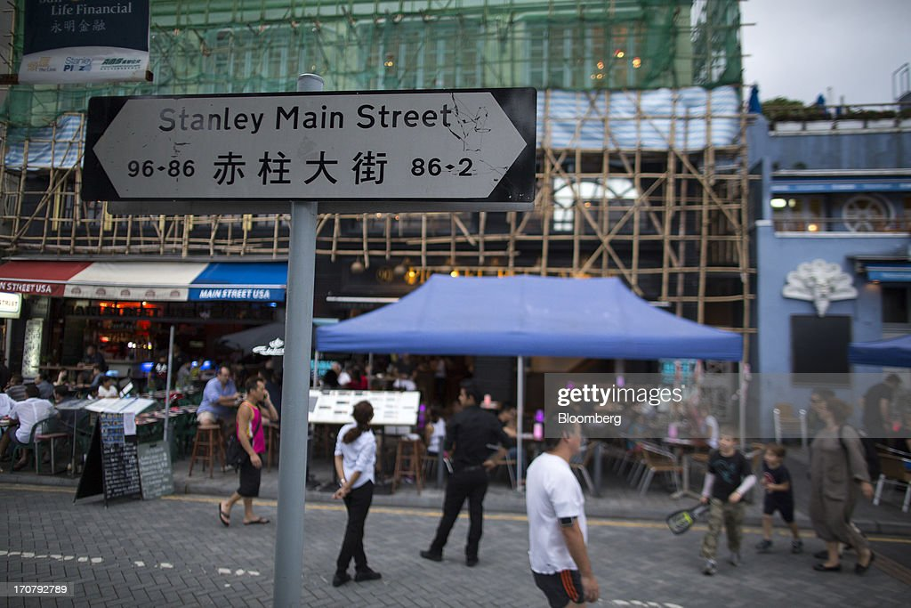 A road sign for Stanley Main Street stands in front of restaurants in the Stanley area of Hong Kong, China, on Sunday, June 16, 2013. A shortage of housing, low mortgage costs and a buying spree by mainland Chinese have led home prices to more than double since the beginning of 2009, shrugging off repeated attempts by the government to curb gains amid an outcry over affordability. Photographer: Jerome Favre/Bloomberg via Getty Images