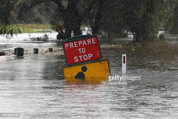 A road sign is seen partially submerged on flood waters on April 22 2015 near Dungog Australia Three people have died and more than 200000 are still...