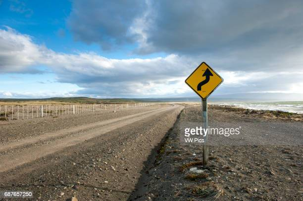 Road sign leading curvy road up ahead Punta Arenas Chile