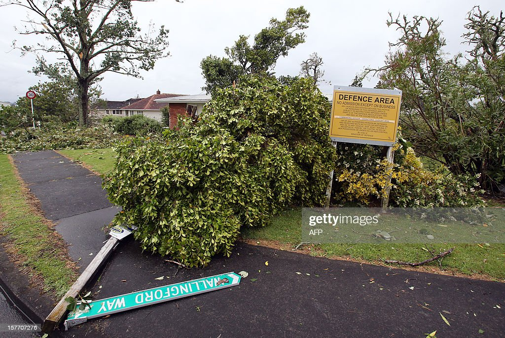 A road sign lies on the pavement on Wallingford Way, the worse hit street in Hobsonville, Auckland on December 6, 2012 after packed wind gusts of up to 110 kilometres (70 miles) per hour, struck suburban Hobsonville in the afternoon. A freak storm described by police as a tornado hit New Zealand's largest city Auckland on December 6 causing 'utter devastation', with three people reportedly killed in ferocious winds. AFP PHOTO / Michael Bradley
