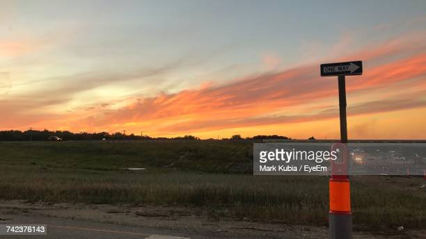 Road Sign On Field Against Sky During Sunset