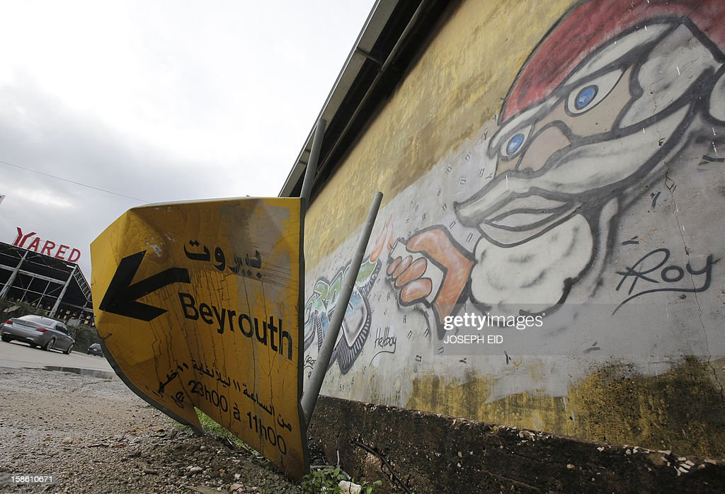 A road sign plate of Beirut lies broken due to high winds at the northern entrance of the Lebanese capital on December 21, 2012 as Lebanon witnessed heavy rain and storms.