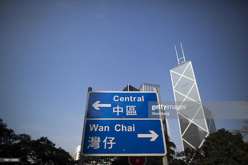 A road sign pointing to the Central and Wanchai areas stands in front of office buildings in the central business district of Hong Kong, China, on Saturday, Jan. 5, 2013. Hong Kong topped the ranks as the most expensive office market by total occupancy cost, according to a report by CBRE Research released on Jan. 7. Photographer: Jerome Favre/Bloomberg via Getty Images