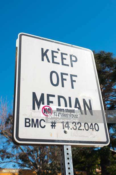 Road sign reading 'Keep Off Median' on which someone has placed a sarcastic decal reading 'No More Stupid Berkeley Signs' on a road median which is a...