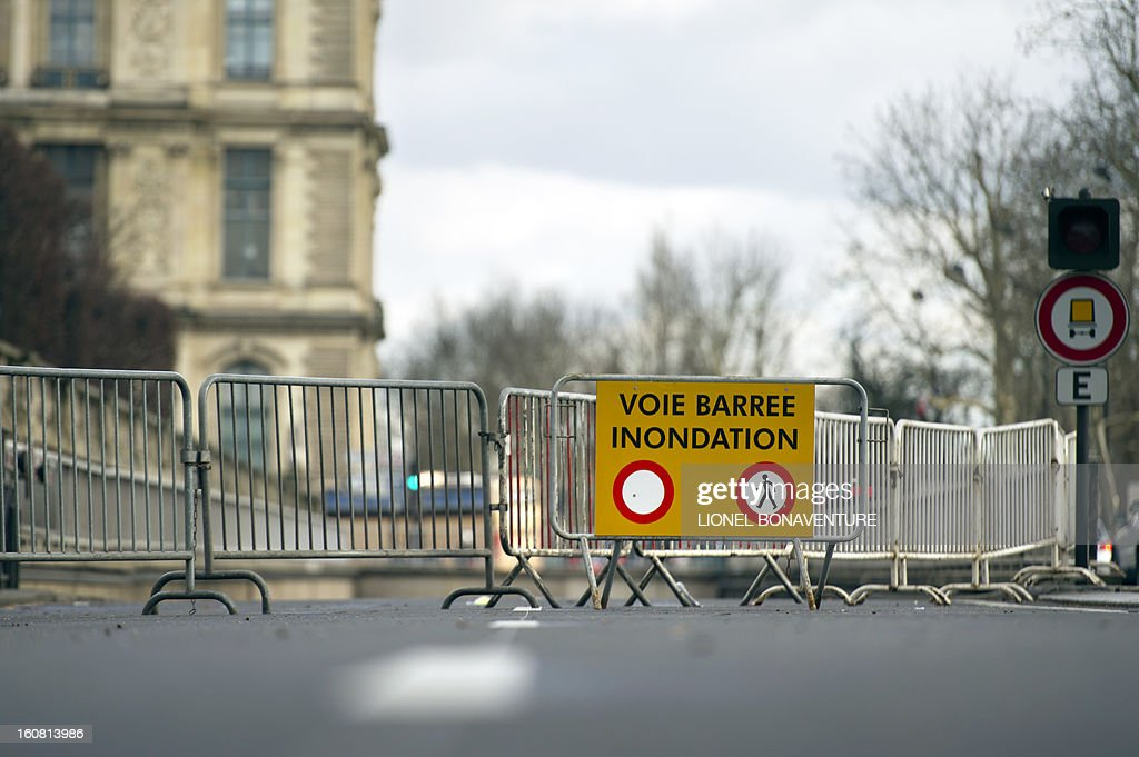 A road sign reading '' road closed, flooding'' and gates are seen on the bank of the Seine river, on February 6, 2013 in Paris. Roads along the river banks are closed to traffic in case of flooding. AFP PHOTO / LIONEL BONAVENTURE