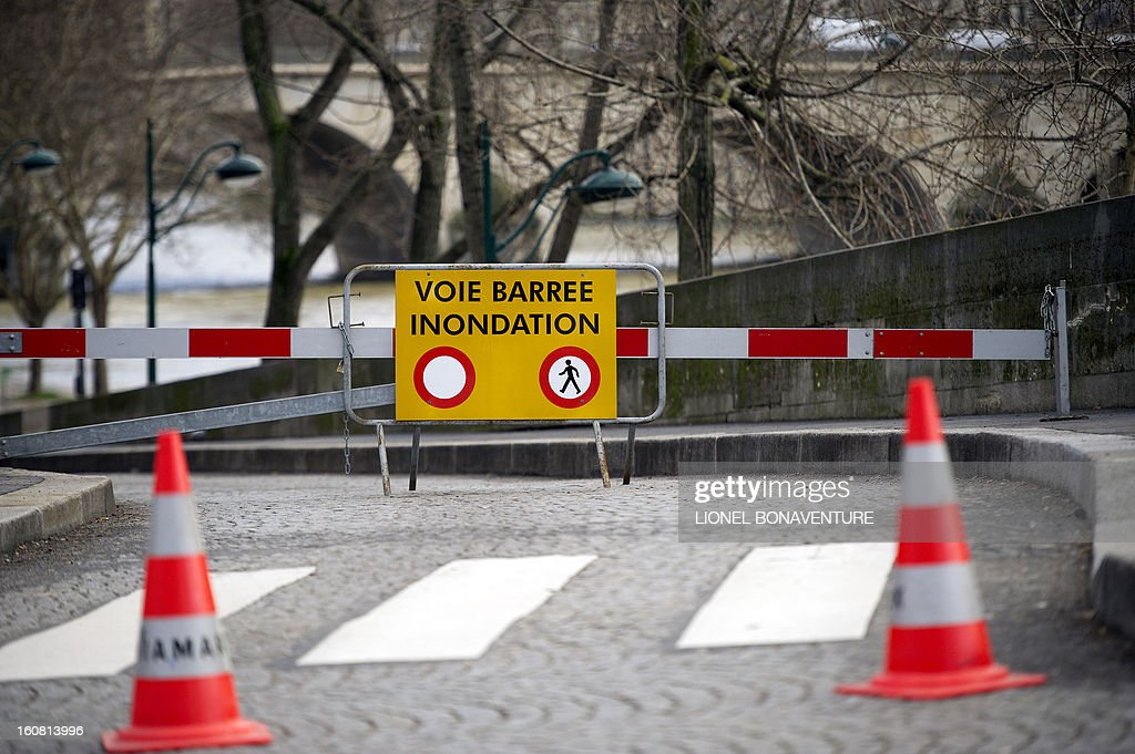 A road sign reading '' road closed, flooding'' is seen on the bank of the Seine river on February 6, 2013 in Paris. Roads along the river banks are closed to traffic in case of flooding.
