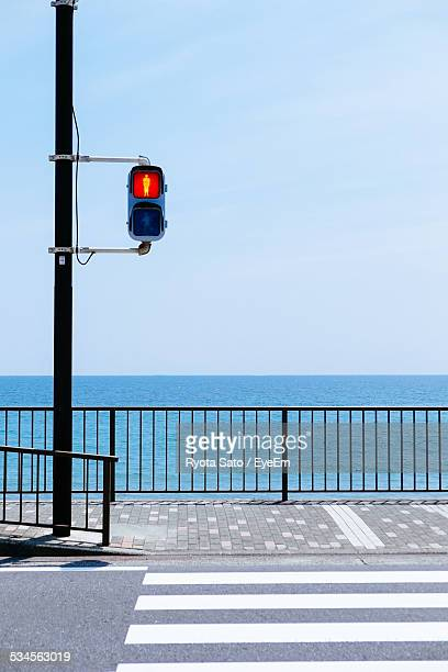 Road Signal On Street By Sea Against Clear Sky