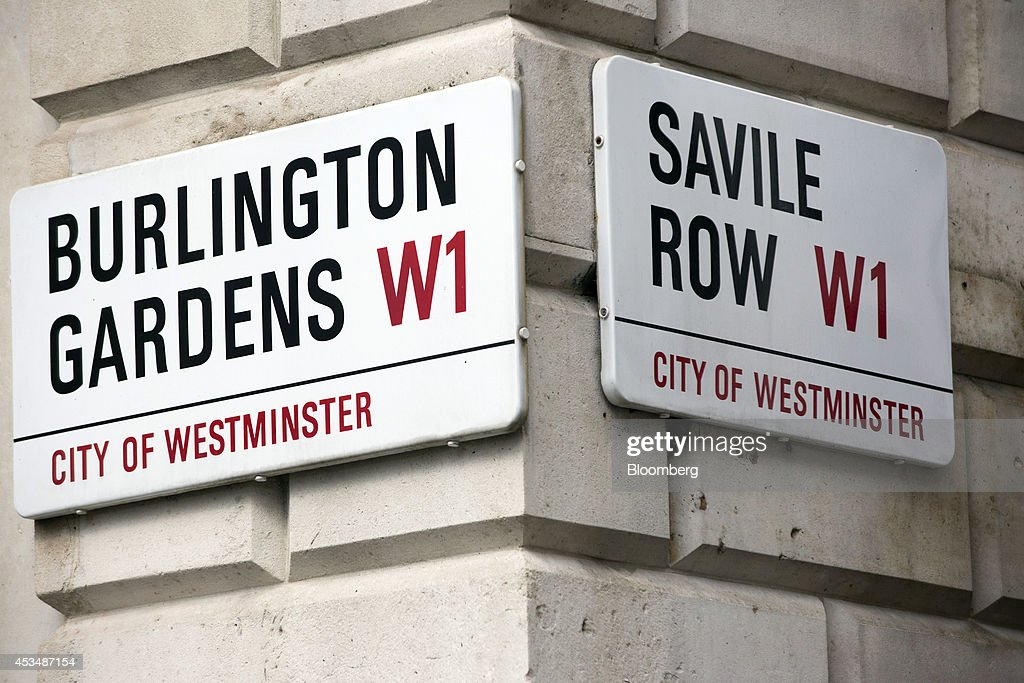 Road signs sit on the corner of a commercial real estate building that forms part of the Pollen Estate, on Burlington Gardens, left, and Savile Row, in London, U.K., on Monday, Aug. 11, 2014. Norway's sovereign wealth fund, Norges Bank Investment Management, the world's largest, bought a stake in the Pollen Estate in London's Mayfair district for 343 million pounds ($576 million), expanding its property holdings in the U.K. capital. Photographer: Jason Alden/Bloomberg via Getty Images