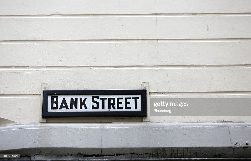 A road street sign for 'Bank Street' sits above a retail store in Leeds, U.K., on Wednesday, Sept. 25, 2013. The parent of Co-operative Bank, which is seeking capital after losses, may avoid being forced to rescue the lender thanks to an accord it struck with regulators last year, according to bondholders. Photographer: Paul Thomas/Bloomberg via Getty Images