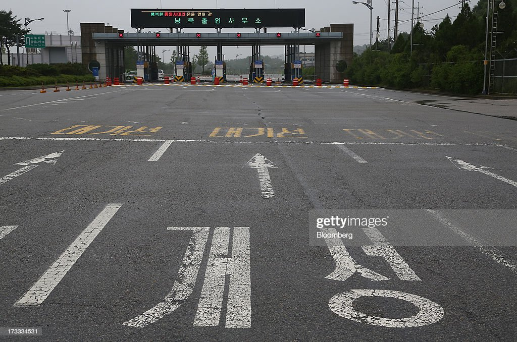 Road surface markings for North Korean city Gaeseong sits in front of a gate at the Customs, Immigration and Quarantine (CIQ) office, near the demilitarized zone (DMZ), in Paju, South Korea, on Friday, July 12, 2013. North Korea notified South Korea today that it has deferred two separate sets of talks on the tours and the family reunions it proposed yesterday, and said it wants to focus on the ongoing dialog to reopen the joint Gaeseong industrial zone, the Souths Unification Ministry said in an e-mailed statement. The two sides yesterday decided to hold talks in Gaeseong on July 15, which will be their third round in one week, on normalizing operations in Gaeseong after the North unilaterally recalled its workers in April. Photographer: SeongJoon Cho/Bloomberg via Getty Images