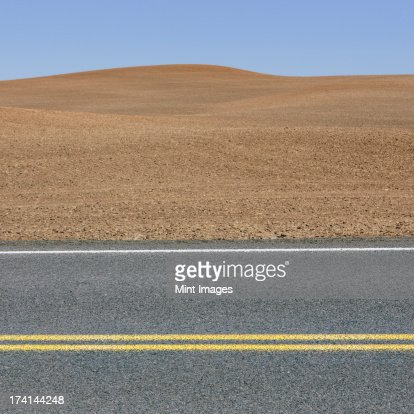 A road through the farming landscape of ploughed fields and farmland near Pullman, Washington state.