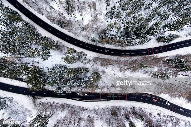 Road through wintery forest aerial view