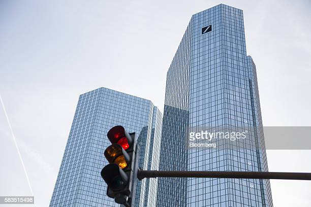 A road traffic light stands in front of the twin tower skyscraper headquarter offices of Deutsche Bank AG stand in Frankfurt Germany on Monday July...