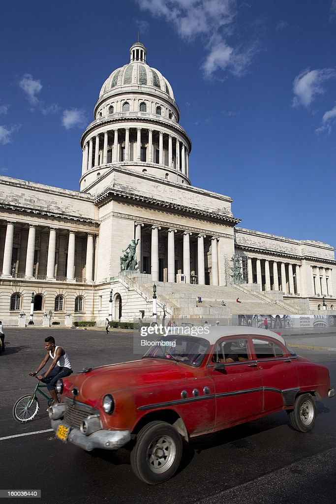 Road traffic passes the national Capitol building in Havana, Cuba, on Thursday, Jan. 17, 2013. In a country where the average monthly salary is $19, according to Cuba's statistics agency, even buying an airplane ticket will be beyond the reach of most of the island's 11 million residents as President Raul Castro begins easing travel rules on the communist island. Photographer: Andrey Rudakov/Bloomberg via Getty Images
