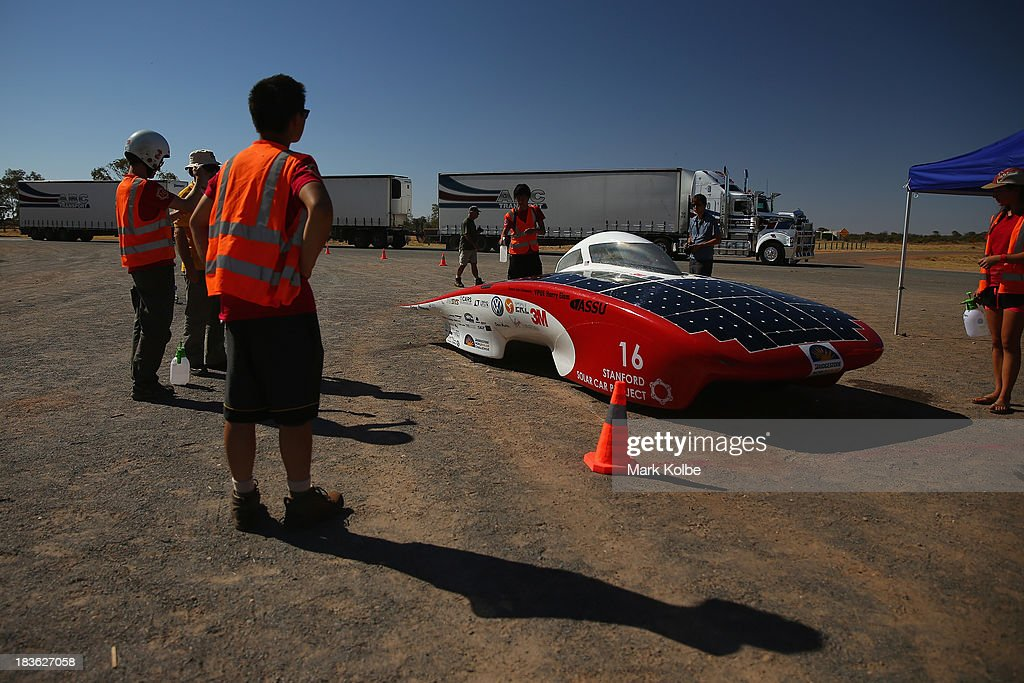 A road trian is seen behind Luminos from the Stanford Solar Car Project, Stanford University in the United States of America during a control stop on Day 3 on October 8, 2013 in Kulgera, Australia. Over 25 teams from across the globe are competing in the 2013 World Solar Challenge - a 3000 km solar-powered vehicle race between Darwin and Adelaide. The race began on October 6th with the first car expected to cross the finish line on October 10th.