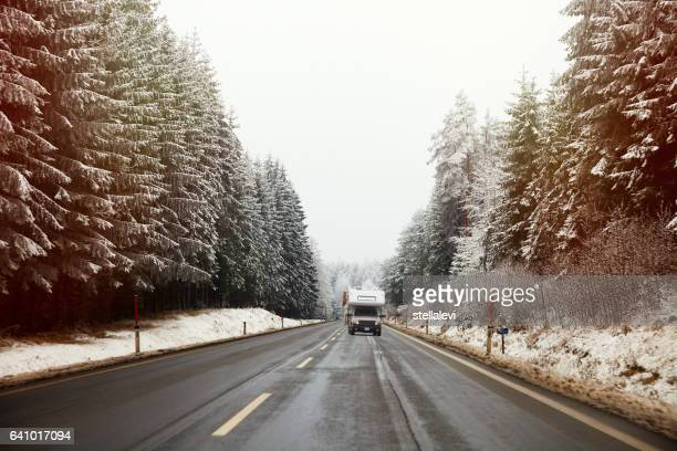 Road trip in winter - mobile home on the highway with snow