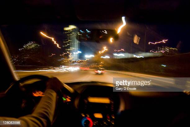 Road viewed from inside car over dashboard at night