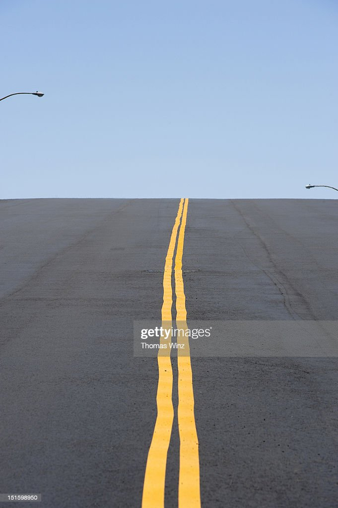 Road with double yellow line over a hill : Stock Photo