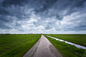 Road with dramatic blue cloudy sky and green grass in cold day in spring. Fantastic landscape in Netherlands. Nature and travel background. Rural road with green fields