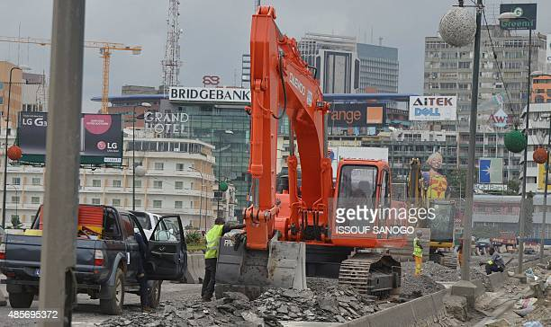 Road workers work the rebuilding site of the General de Gaulle bridge in Abidjan on August 28 2015 The government began rehabilitation works of the...