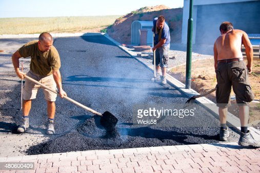 Road workers working with hot asphalt : Stock Photo