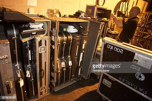 A roadie belonging to the crew of British rock and roll band Status Quo starts packing up sound equipment and the guitars of Rick Parfitt and Francis...
