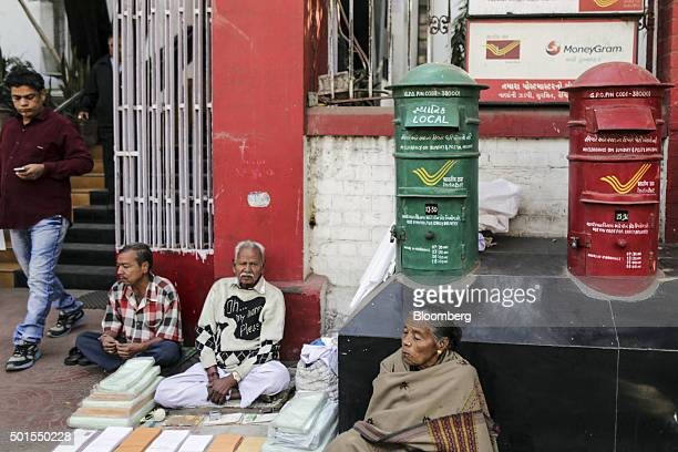 Roadside envelope vendors sit waiting for customer outside a post office in the Relief Road area of Ahmadabad Gujarat India on Monday Dec 14 2015...