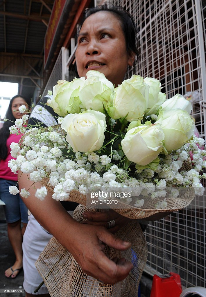 A roadside florist arranges flowers on Valentine's Day in Manila on February 14, 2016. Although not an official holiday, Valentine's Day is widely celebrated in this largely Christian nation with acts of affection and romance such as sweethearts going on special dates or giving expensive presents. AFP PHOTO / Jay DIRECTO / AFP / JAY DIRECTO
