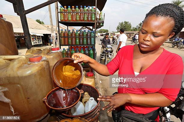 A roadside fuel vendor fills plastic bottles with gasoline for sale in KDare Nigeria on Wednesday Jan 13 2016 Twenty years after the oilpollution...