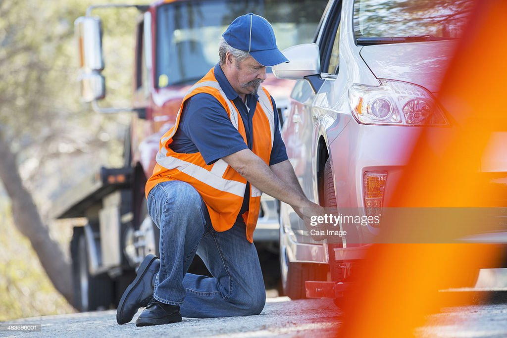 Roadside mechanic repairing flat tire