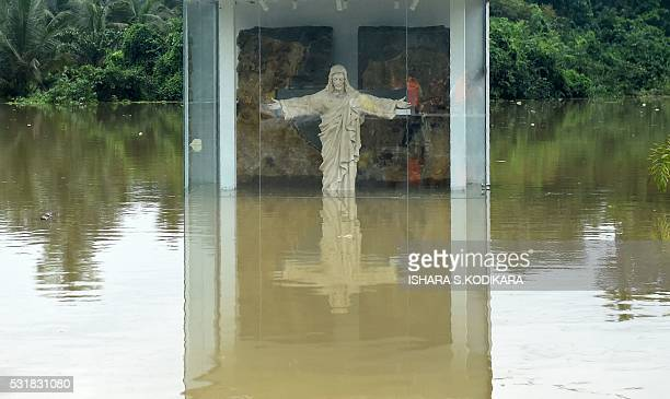A roadside statue of Jesus Christ is submerged by floodwaters in Pugoda about 35 kms from capital Colombo on May 17 2016 Heavy rains claimed three...