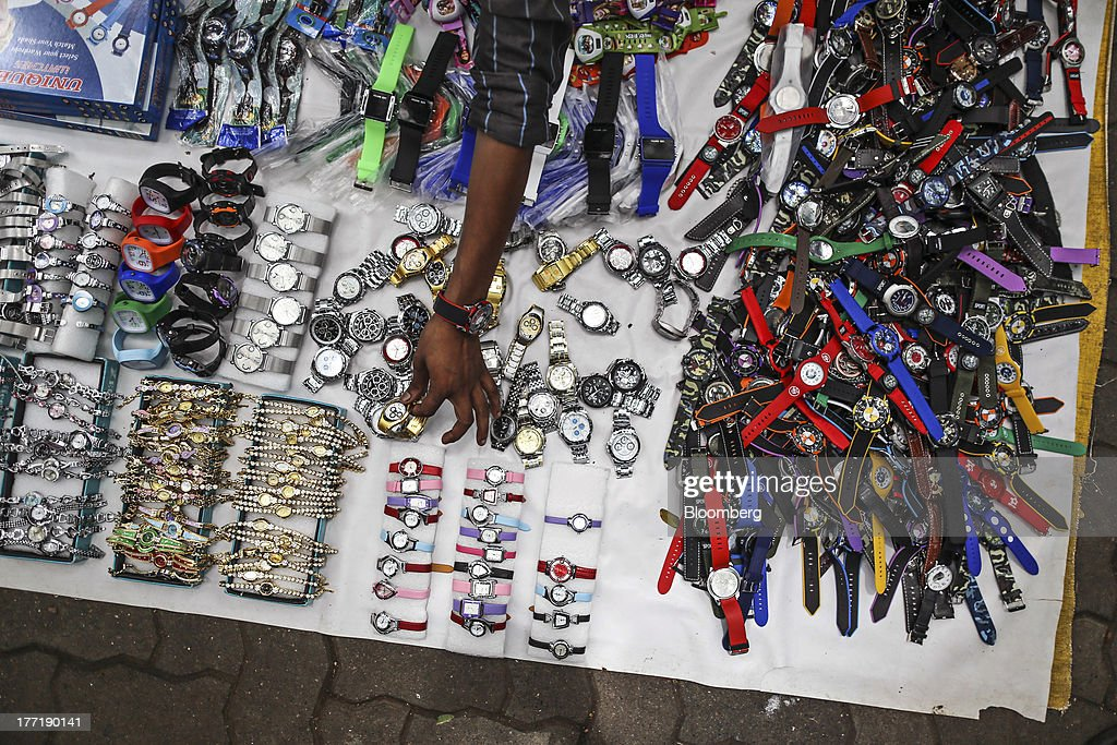 A roadside vendor arranges a watch display in Mumbai, India, on Wednesday, Aug. 21, 2013. The prospect of an indecisive 2014 election in India is eroding confidence among global investors that the government can stop the rupees worst drop in more than two decades. Photographer: Dhiraj Singh/Bloomberg via Getty Images