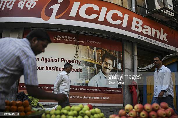 A roadside vendor arranges fruits at a stall as pedestrians walk past a ICICI Bank Ltd branch in Mumbai India on Friday Jan 27 2017 While economists...