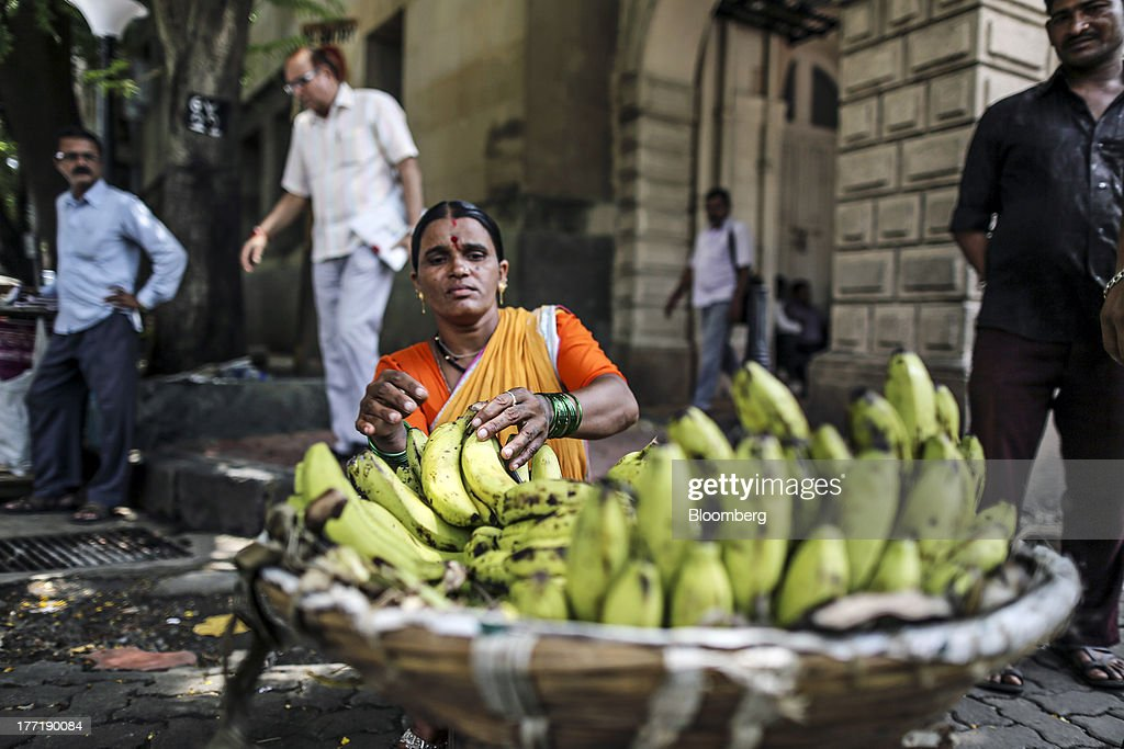 A roadside vendor sells bananas outside The Asiatic Society of Mumbai Library in Mumbai, India, on Wednesday, Aug. 21, 2013. The prospect of an indecisive 2014 election in India is eroding confidence among global investors that the government can stop the rupees worst drop in more than two decades. Photographer: Dhiraj Singh/Bloomberg via Getty Images