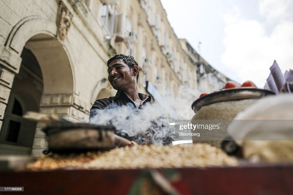 A roadside vendor sells peanuts outside The Asiatic Society of Mumbai Library in Mumbai, India, on Wednesday, Aug. 21, 2013. The prospect of an indecisive 2014 election in India is eroding confidence among global investors that the government can stop the rupees worst drop in more than two decades. Photographer: Dhiraj Singh/Bloomberg via Getty Images